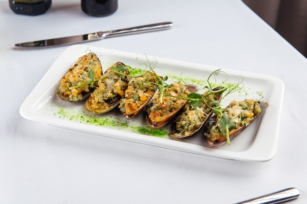 Cozze appetitose con ripieno sul tavolo bianco
