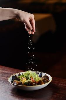 Cozze con semi di sesamo in un piatto su un fondo di legno