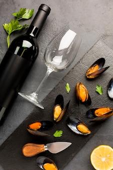 Cozze cotte e bottiglia di vino piatte