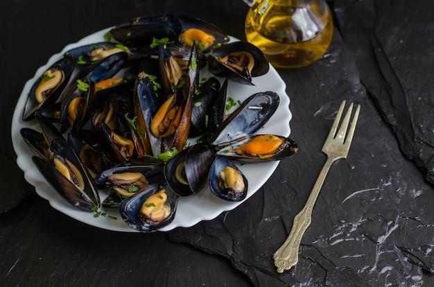 Cozze cucinate deliziose dei frutti di mare con le erbe e l'olio d'oliva su un piatto bianco su fondo nero. cucina mediterranea