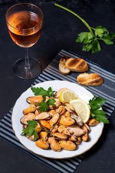 Cozze deliziose del primo piano con bicchiere di vino