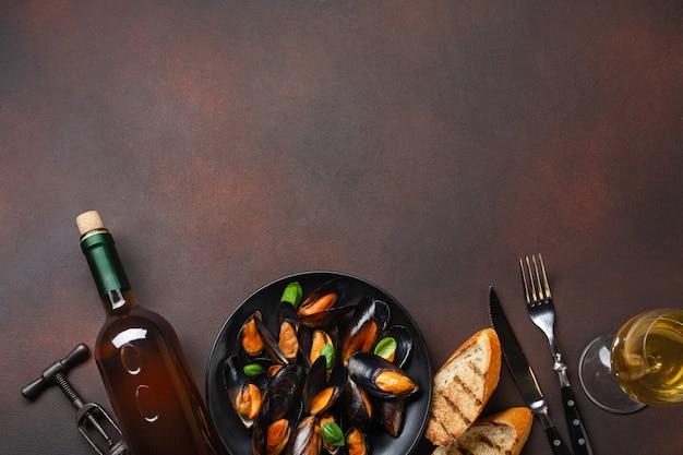 Cozze di frutti di mare e foglie di basilico in un piatto nero con bottiglia di vino, bicchiere da vino, cavatappi, fette di pane, forchetta e coltello su sfondo arrugginito