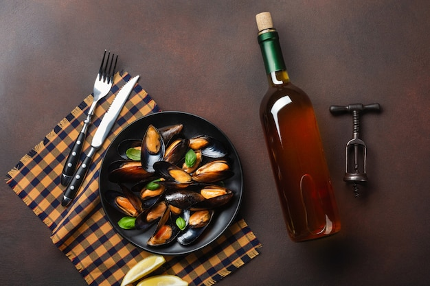 Cozze di frutti di mare e foglie di basilico in un piatto nero con bottiglia di vino, cavatappi e forchetta sul coltello