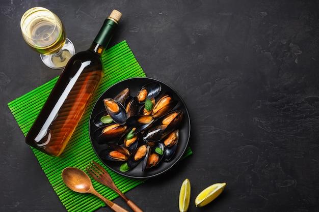 Cozze di frutti di mare, foglie di basilico in un piatto nero con vino bootle, bicchiere da vino e limone