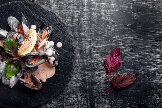 Cozze di frutti di mare in salsa di panna con limone e basilico su una lastra di pietra e nero