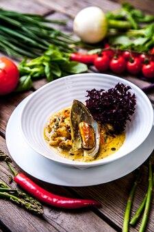 Cozze in cottura con limone ed erbe aromatiche in pentola di terracotta sul tavolo di legno