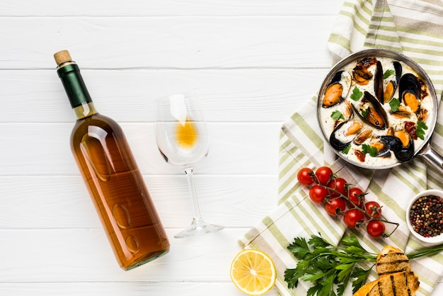 Cozze piatte in salsa bianca e bottiglia di vino