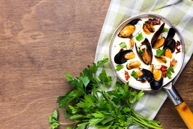 Cozze piatte in salsa bianca e prezzemolo sulla tovaglia con copyspace