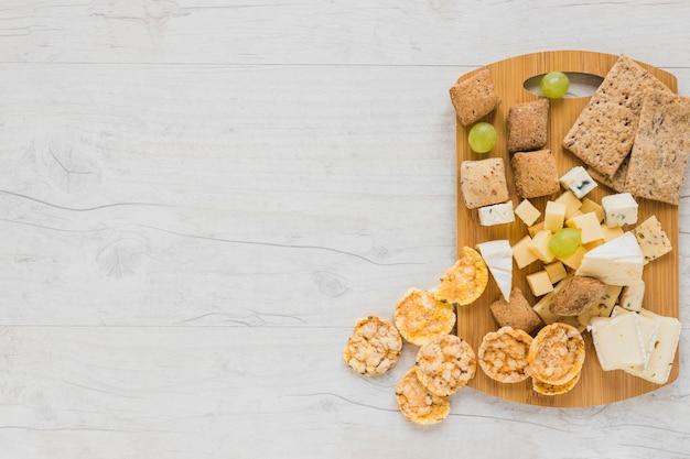 Cracker, blocchi di formaggio, uva e pane croccante e biscotti sul tagliere sopra la scrivania