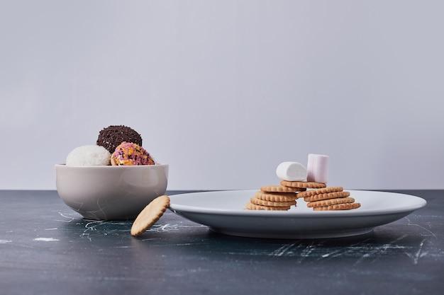 Cracker con biscotti marshmallow in piatti bianchi sul blu.