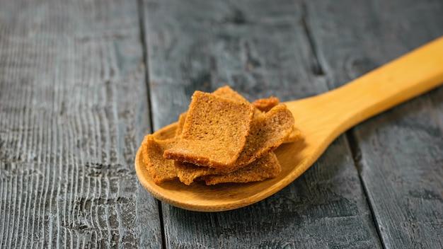 Cracker con erbe in un cucchiaio di legno su un tavolo in legno nero.