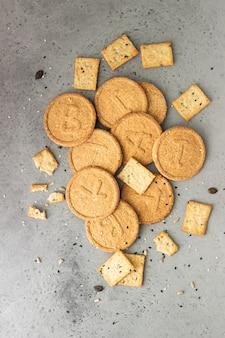 Cracker croccanti sottili sottili con semi su calcestruzzo grigio.
