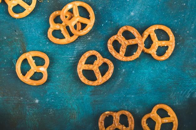Cracker della ciambellina salata su un fondo blu di legno