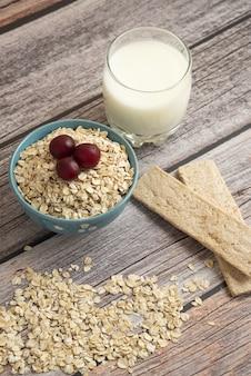 Cracker di farina d'avena, cereali con frutti di bosco e una tazza di latte sul tavolo