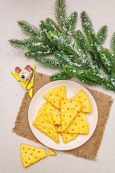 Cracker di formaggio festivo, concetto di snack di capodanno. biscotti, figura di topo, ramo di abete, neve artificiale, tovagliolo di tela di sacco.