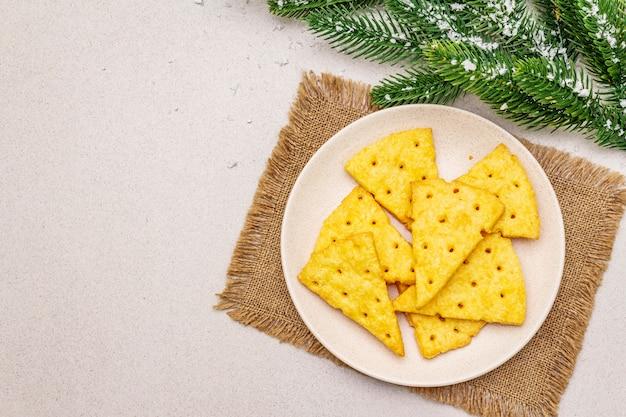 Cracker di formaggio festivo, concetto di snack di capodanno. biscotti, ramo di abete, neve artificiale, tovagliolo di tela di sacco. sfondo di cemento di pietra
