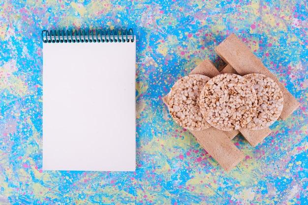 Cracker di grano e mais su un blu con un taccuino da parte.