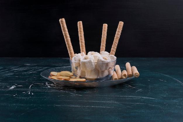 Cracker e bastoncini di cialda con lokum turco in un piatto di vetro su sfondo nero