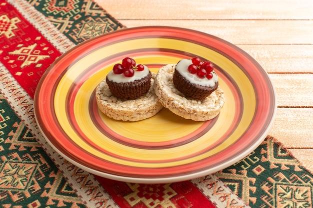 Cracker e torte con mirtilli rossi in cima all'interno del piatto colorato su crema rustica