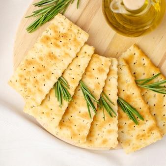 Cracker fatti in casa con rosmarino e olio d'oliva su tavola di legno