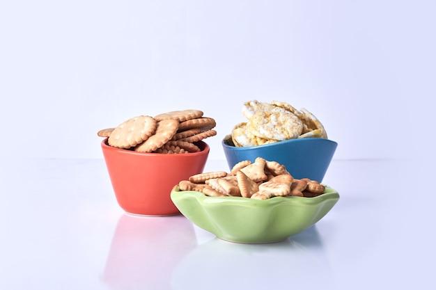 Cracker in tazze colorate su bianco.