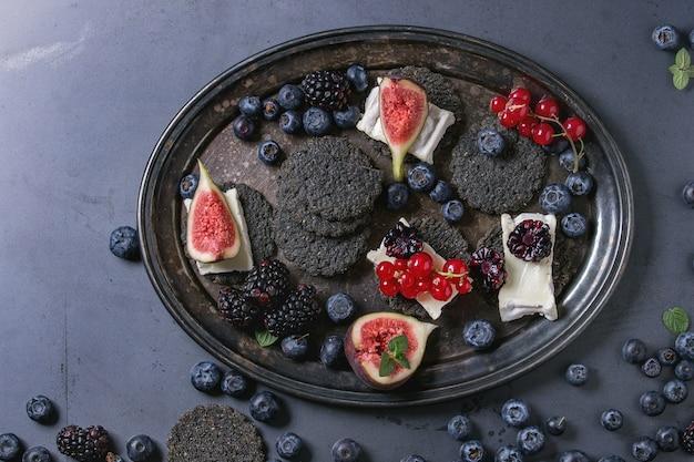 Cracker nero con formaggio e frutti di bosco