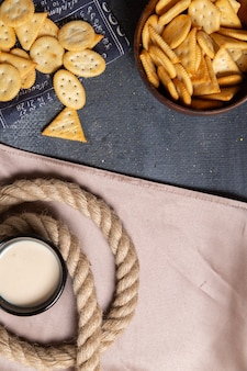 Cracker salati con vista in lontananza superiore con latte e corde sulla foto di spuntino croccante di sfondo grigio