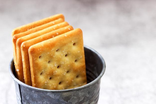 Cracker salati rettangolari in un secchio zincato su uno sfondo grigio.