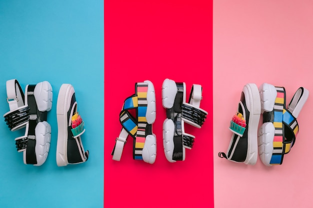 Cracovia, polonia - 25 aprile 2019: set di scarpe femminili alla moda. sandali donna multicolore alla moda estate su zeppa alta su sfondo blu e rosa. calzature eleganti e alla moda per ragazze moderne.