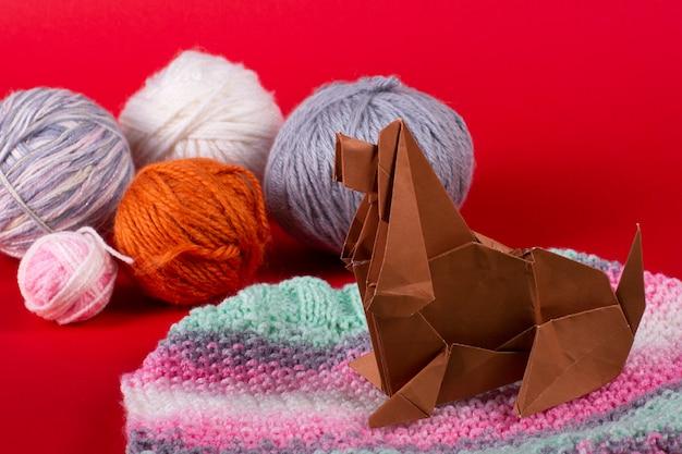 Craft origami concetto di una casa accogliente - un cane con gomitoli di lana si siede su una sferza. fine fatta a mano della carta patinata su