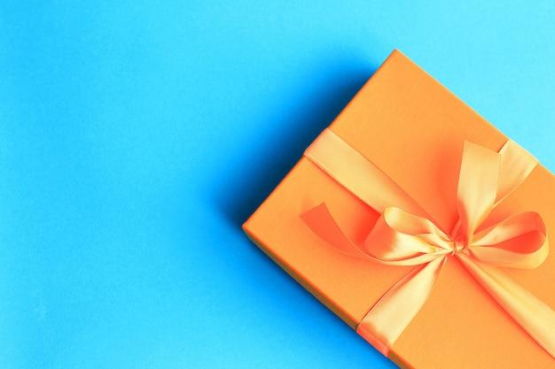 Craft regalo di carta con nastro arancione su sfondo blu scuro con spazio di copia.
