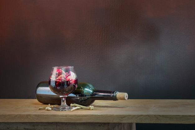 Crani nel bicchiere di sangue e vino sul tavolo di legno.