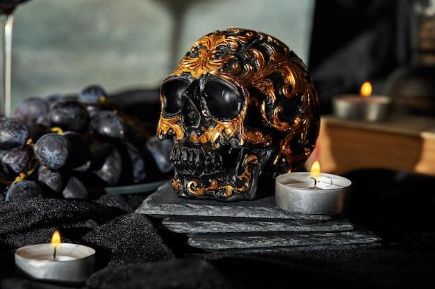 Cranio del bordo di halloween, candele su un'oscurità. halloween
