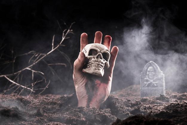 Cranio della holding della mano dello zombie di halloween al cimitero