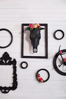 Cranio nero di un cervo e corna su una parete bianca in legno con cornici vuote per quadri. il concetto di decorare una parete bianca in legno in stile gotico in salotto. decor, vintage, moderno