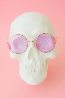 Cranio umano bianco con occhiali rosa. avvicinamento