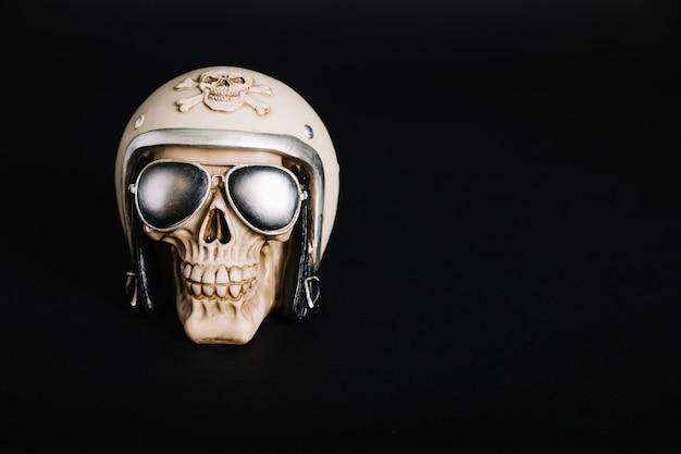Cranio umano indossando casco e occhiali da sole