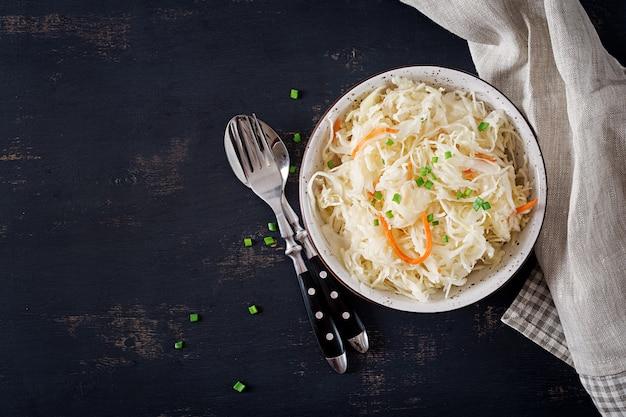 Crauti con la carota e le spezie in ciotola su oscurità