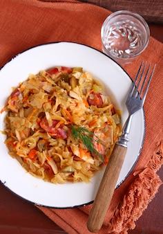 Crauti con salsiccia cipolle e carote in un piatto bianco
