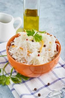 Crauti fatti in casa con condimenti in una ciotola d'arancia. probiotici naturali, cibo sano