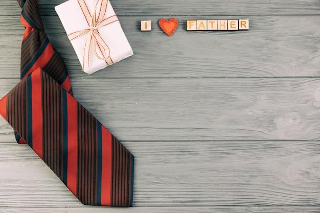 Cravatta a strisce vicino al regalo e io amo il titolo del padre