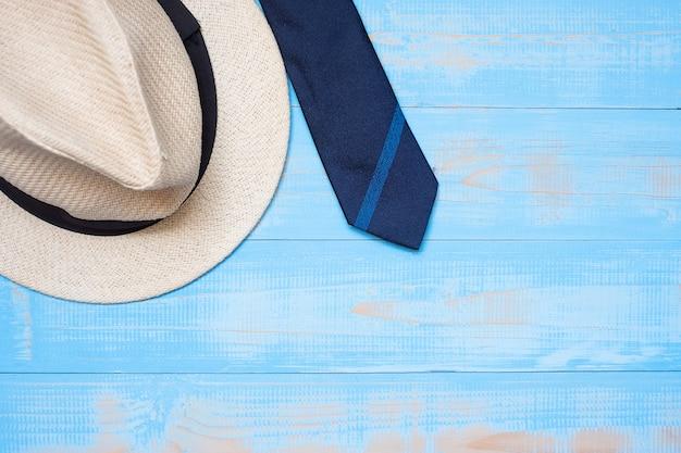 Cravatta blu con il cappello su fondo di legno con lo spazio della copia per testo