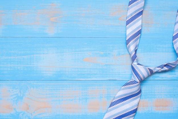 Cravatta blu su fondo di legno con lo spazio della copia per testo.