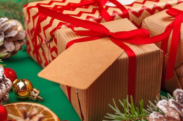 Crea regali di natale con nastri rossi su sfondo decorato di natale