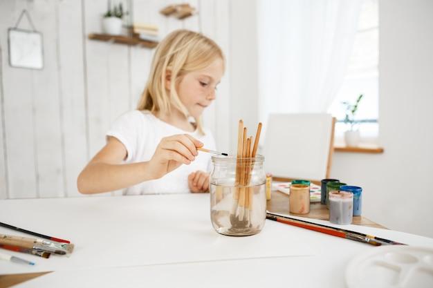 Creativa piccola ragazza bionda con le lentiggini che lava la spazzola in barattolo d'acqua durante la lezione di arte