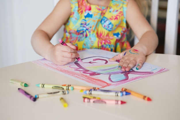 Creatività dei bambini. la ragazza del piccolo bambino disegna con le matite di cera a casa. il concetto di apprendimento a distanza online per il periodo di quarantena globale.