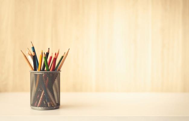 Creatività delle matite variopinte in astuccio per le matite sul fondo di legno dello scrittorio della tabella