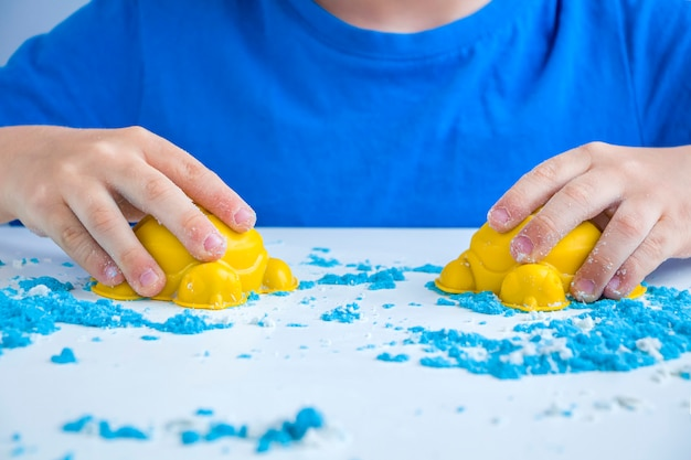 Creatività per bambini. giochi di sabbia cinetica per lo sviluppo del bambino a casa. terapia della sabbia. mani dei bambini che producono stampi. messa a fuoco selettiva, retroilluminazione