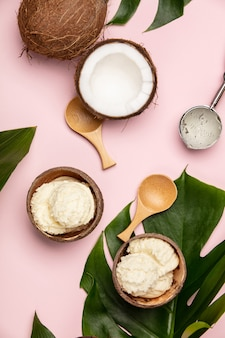 Creativo piatto disteso con gelato al cocco e piante tropicali