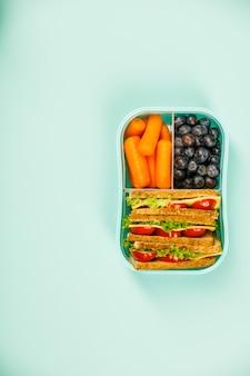 Creativo piatto disteso con pranzo sano in contenitore blu